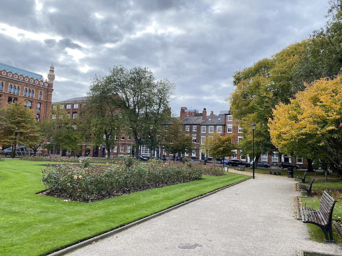 Park Square with flowers, grass, trees, and benches
